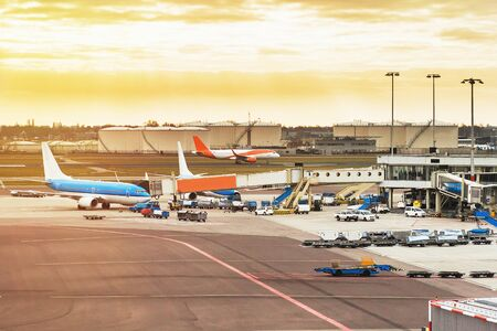 Airport with airplanes at the terminal gate ready for takeoff, international airport during sunset