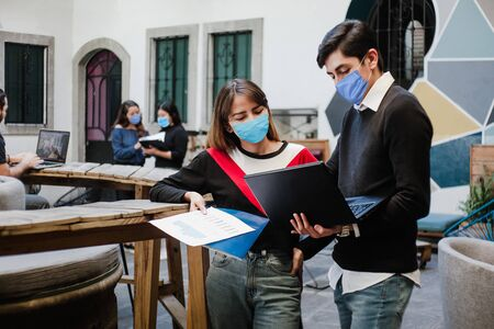 Latin people working and wearing medical face mask for social distancing in new normal situation protecting and preventing the infection of covid-19, mexican coworkers