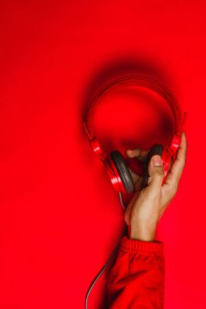 hand holding Red headphones on red background. Music concept Фото со стока