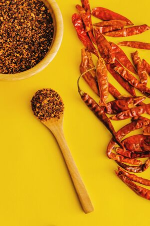 Dried red chili peppers Guajillo and chili powder spice on yellow background