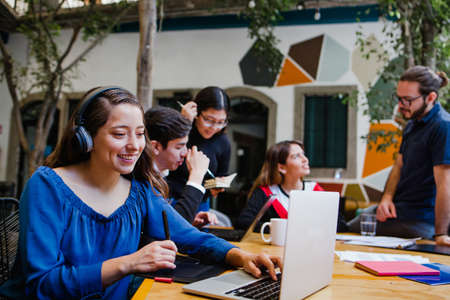 Young latin woman working with computer and her coworkers at the office or coworking in Mexico or South America, Mexican teamwork Фото со стока
