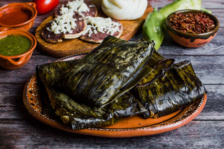 Tamal from Oaxaca called Tamales Oaxaqueños is a traditional Mexican dish made with corn dough, chicken or pork wrapped in a banana leaves in Mexico Фото со стока