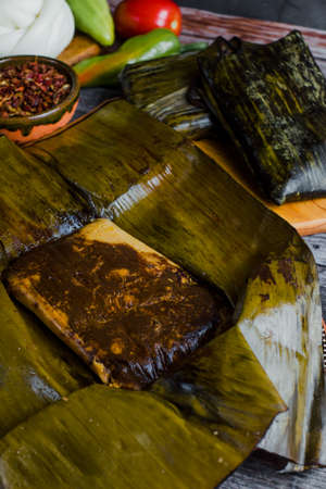 Tamal from Oaxaca called Tamales Oaxaqueños is a traditional Mexican dish made with corn dough, chicken or pork wrapped in a banana leaves in Mexico Фото со стока - 153612530