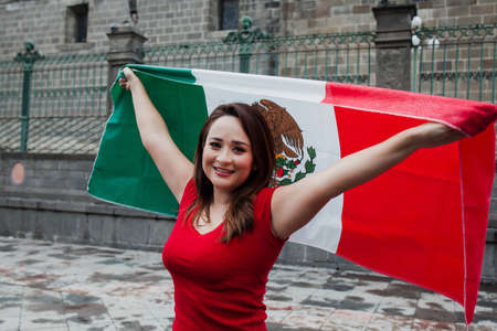 mexican woman at independence day in Mexico holding a flag of mexico Фото со стока - 155859402
