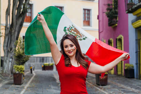 mexican woman at independence day in Mexico holding a flag of mexico Фото со стока