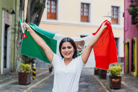 mexican woman at independence day in Mexico holding a flag of mexico Фото со стока - 155859404