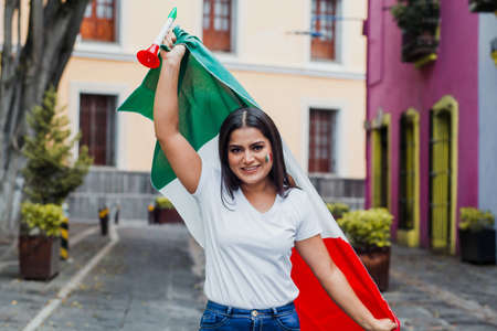 mexican woman at independence day in Mexico holding a flag of mexico Фото со стока - 155859408