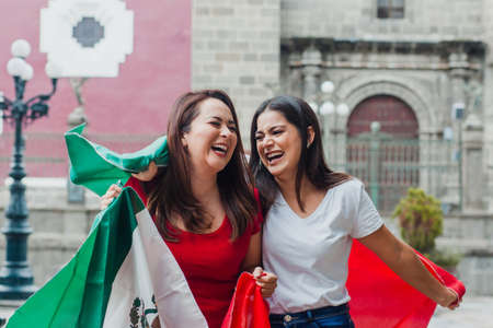 mexican girls friends at independence day in Mexico holding a flag of mexico