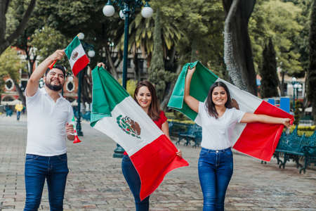 Mexican people with flag in Mexican independence day in Mexico Фото со стока - 155859413