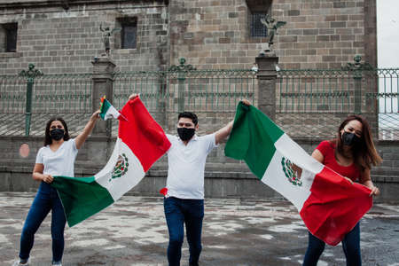 Mexican people with flag in Mexican independence day in Mexico Фото со стока - 155859414