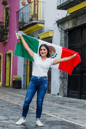 mexican woman at independence day in Mexico holding a flag of mexico Фото со стока - 155859416