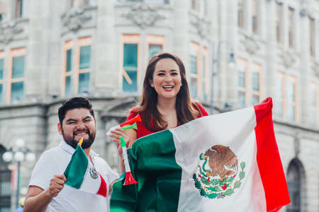 mexican friends at independence day in Mexico holding a flag of mexico Фото со стока - 155859420