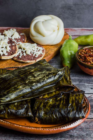 Mexican Tamales Oaxaquenos in banana leaves traditional from Oaxaca Mexico on wooden background