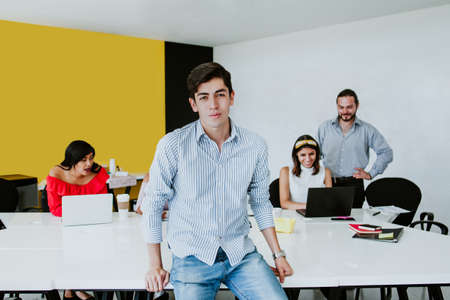 Portrait of young latin man sitting at his desk in the office in Mexico Latin America