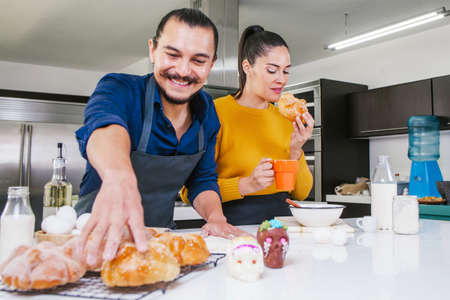 Mexican people baking and eating bread called pan de muerto traditional from Mexico in Halloween Фото со стока