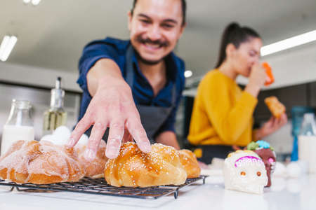 Mexican man baking bread called pan de muerto traditional from Mexico in Halloween