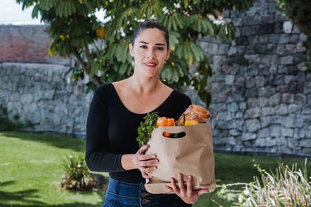 woman holding shopping paper bag with organic fresh food