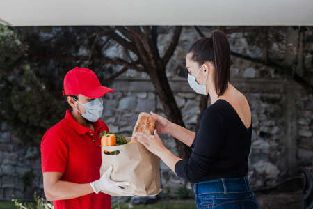 Mexican deliver man wearing face mask in red uniform handling bag of food, fruit, vegetable give to female costumer in front of the house. Grocery delivery service during covid19