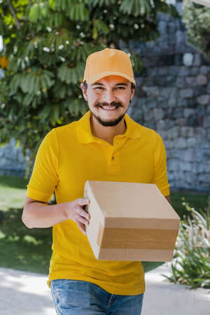Latin delivery man holding and carrying a cardbox in Mexico Фото со стока - 156830935