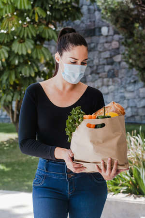woman holding shopping paper bag with organic fresh food with facemask, delivery service during covid19 pandemic