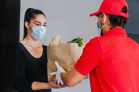 Mexican deliver man wearing face mask in red uniform handling bag of food, fruit, vegetable give to female costumer in front of the house. Grocery delivery service during covid19 Фото со стока - 156830941