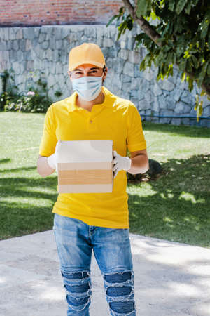 Latin delivery man with mask holding and carrying a cardbox in quarantine coronavirus pandemic