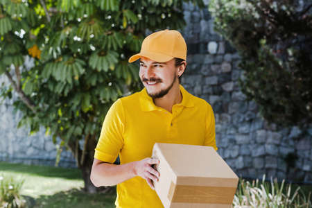 Latin delivery man holding and carrying a cardbox in Mexico