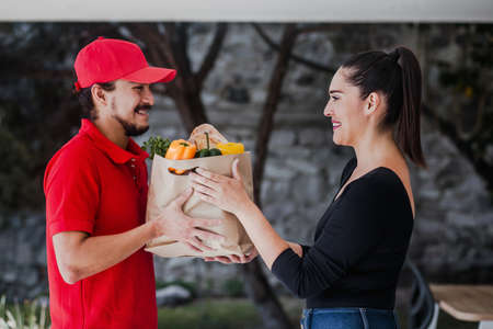 Latin deliver man in red uniform handling bag of food, fruit, vegetable give to female costumer in front of the house. Postman grocery delivery service in Mexico Фото со стока