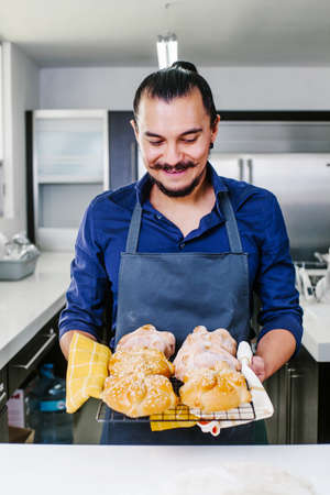 Mexican man cooking Pan de Muerto Traditional bread for day of the dead in Mexico Фото со стока - 157330375