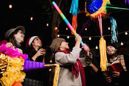 Mexican Posada group of latin friends breaking a Piñata celebrating Christmas in Mexico city