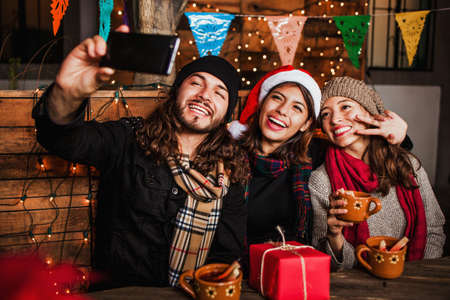 Mexican Posada friends celebrating Christmas in Mexico and having fun taking a photo selfie