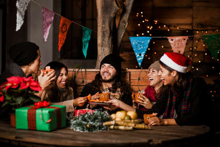 Mexican Posada friends celebrating Christmas eve in Mexico and having fun in winter party