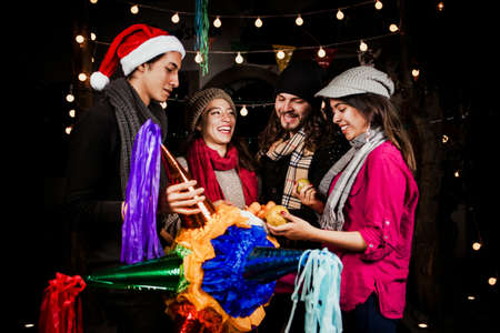 Mexican Posada group of latin friends breaking a Piñata celebrating Christmas in Mexico city Stock Photo
