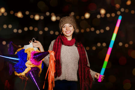 Mexican Woman Holding a colorful Piñata celebrating Christmas in a traditional Posada in Mexico City Stock Photo