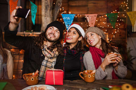 Mexican Posada friends celebrating Christmas in Mexico and taking a photo selfie
