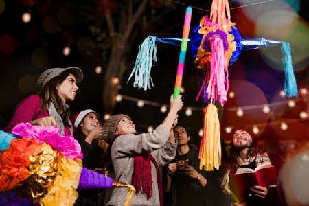 Mexican People breaking a piñata celebrating a Posada in Christmas Mexico
