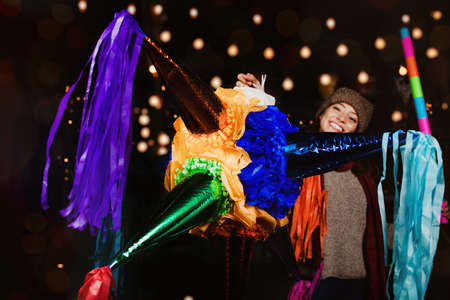 Mexican Woman Holding a colorful Piñata celebrating Christmas in a traditional Posada in Mexico City