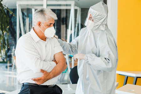 old latin man receiving vaccine shot for a mexican doctor woman with facemask for coronavirus pandemic in Mexico city