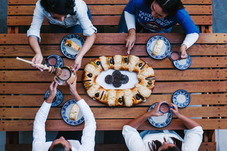 Mexican people eating Rosca de reyes or Epiphany cake, Roscon de reyes with traditional mexican chocolate cup in Mexico top view
