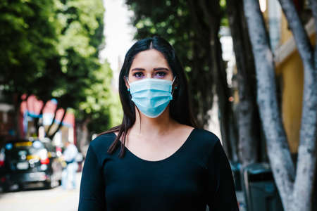 portrait of Mexican business woman with face mask in the streets in a colonial city of Latin America for coronavirus pandemic