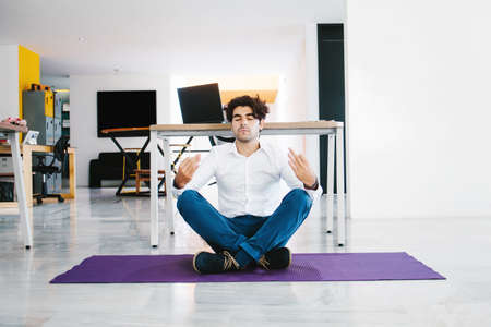 young mexican man meditating and doing yoga in office in Latin America Фото со стока