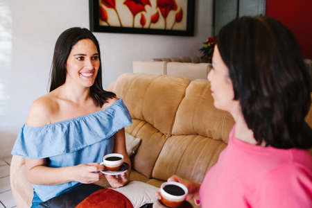 Latin women friends hanging out and drinking coffee in home in Mexico city