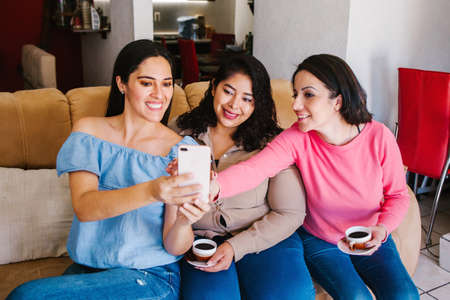Latin women friends taking a selfie photo and drinking coffee in home in Mexico city