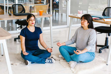 latin business people meditating and doing yoga in office in Mexico city