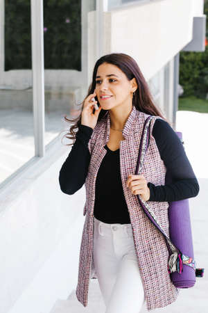 young mexican business woman or student practicing breathing yoga exercises at workplace, office meditation holding a cellphone on Mexico city or latin america