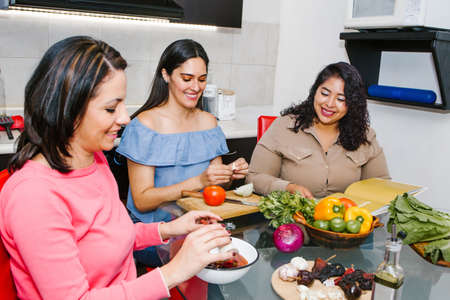 Three Hispanic Female Friends cooking vegetables in a Mexican Kitchen Together in Latin America Stock Photo