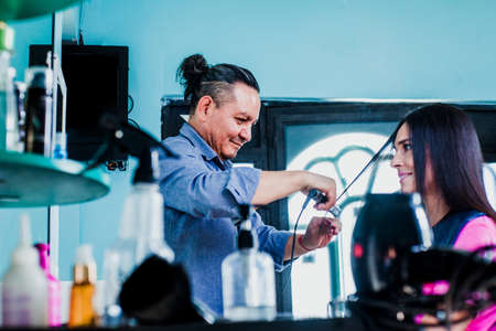 latin man working as a hairdresser and cutting hair of a female customer in a beauty salon small business in Mexico city