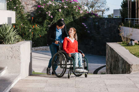 Happy young latin woman in wheelchair and her friend having fun outdoors in Mexico