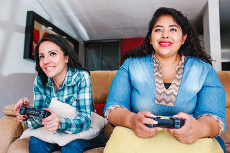 Two latin female best friends sitting at home playing games on console in Mexico Foto de archivo