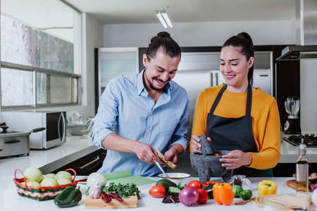 latin couple cooking mexican sauce together in their kitchen at home in Mexico city